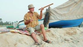 De hogere mens zit op het strand en het maken van fluit door handen stock video