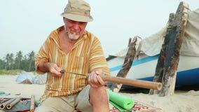De hogere mens zit op het strand en het maken van fluit door handen stock videobeelden