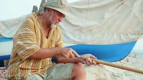 De hogere mens zit op het strand en het maken van fluit door handen stock footage