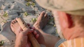 De hogere mens zit op het strand en het maken van fluit door handen, close-up stock videobeelden