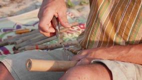 De hogere mens zit op het strand en het maken van fluit door handen, close-up stock video
