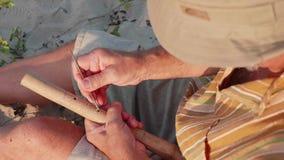 De hogere mens zit op het strand en het maken van fluit door handen, close-up stock footage