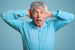 De hogere midden oude grijze haired mens houdt handen achter hoofd, staart in ongeloof, draagt formeel overhemd, stelt tegen blau royalty-vrije stock foto