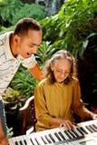 De hogere moeder en de zoon zingen en spelen piano Stock Foto's