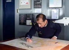 De hogere Navigator van het schip ` via Australis ` die de overzeese route op de kaart van Kaaphoorn bedekken Stock Foto