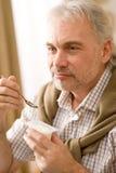 De hogere rijpe mens eet yoghurtsnack Royalty-vrije Stock Fotografie
