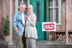 De hogere sleutels van de paarholding van hun nieuw huis en status op portiek Royalty-vrije Stock Foto's