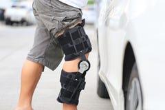 De hogere steun van de de kniesteun van de mensenslijtage op been die zich bij het autoparkeerterrein, Medische en gezondheidszor royalty-vrije stock afbeelding