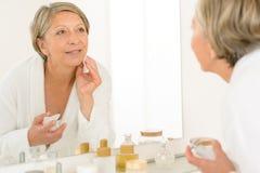 De hogere vrouw bekijkt zich badkamersspiegel stock afbeeldingen