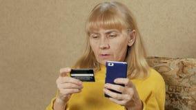 De hogere vrouw betaalt voor aankopen in de Internet-bankcreditcard Zij introduceert zorgvuldig een creditcardaantal aan stock video