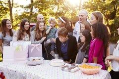 De hogere vrouw blaast uit kaarsen bij haar partij van de verjaardagstuin royalty-vrije stock foto
