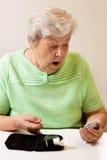 De hogere vrouw in de maatregel van de bloedsuiker is verrast Royalty-vrije Stock Afbeeldingen