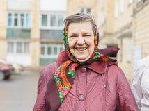 De hogere vrouw in een headscarf glimlacht royalty-vrije stock foto's