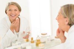 De hogere vrouw het glimlachen bezinning van de badkamersspiegel stock foto's