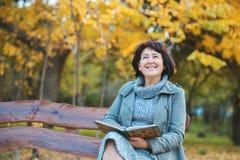 De hogere vrouw leest het boek en droomt in het park Stock Foto's
