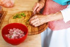 De hogere vrouw overhandigt hakkende groenten op een houten raad in de keuken stock afbeelding