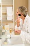 De hogere vrouw past samenstellingspoeder in badkamers toe royalty-vrije stock afbeeldingen