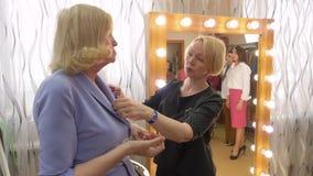 De hogere Vrouw probeert de Winkel van de de Besprekingsmanier van de Oorringsstilist stock video