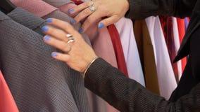De hogere vrouw winkelt kiezend een blouse in een kledingsopslag, overhandigt close-up stock videobeelden