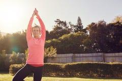 De hogere vrouw zich in openlucht in yoga stelt voor saldo en concentreert stock afbeelding