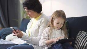 De hogere vrouw zit op bank en bekijkt smartphone terwijl het jonge meisje op iets let interesserend op tablet stock footage