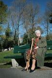 De hogere vrouw zit op een bank Stock Foto's