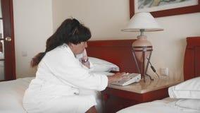 De hogere vrouwenzitting op een bed in een hotel in een witte badjas en neemt de telefoon en de wijzerplaten op Langzame Motie stock video