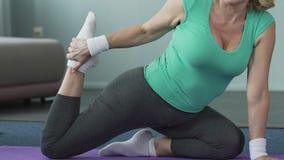De hogere vrouwenzitting op geschiktheidsmat, die haar been, yoga uitrekken stelt, flexibiliteit stock video