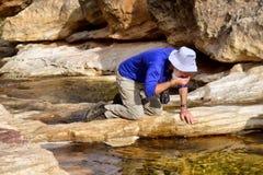 De hogere wandelaar drinkt water van bergrivier Royalty-vrije Stock Foto