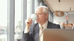 De hogere zakenman bekijkt uit het venster de koffie stock footage