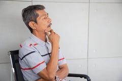 De hogere zakenman van Azië zit en denkend stock foto