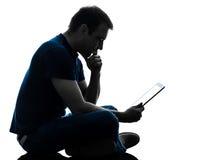 De holding die van de mensenzitting op digitaal tabletsilhouet letten Stock Foto