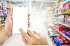 De holding die van de mensenhand slimme telefoon in supermarkt met behulp van royalty-vrije stock afbeeldingen