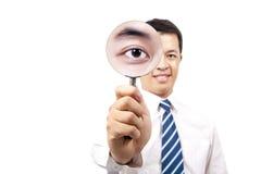 De holding Magnifier van de zakenman Stock Afbeelding