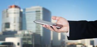 De Holding Smartphone van de Businessmanshand met Commerciële Stad en Collectieve Gebouwen op Achtergrond stock afbeeldingen
