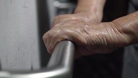 De holding van de bejaardehand op leuning voor steun stock footage