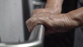 De holding van de bejaardehand op leuning voor steun stock video