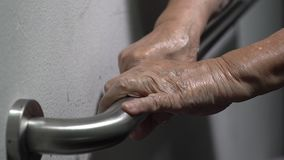 De holding van de bejaardehand op leuning voor steun stock videobeelden