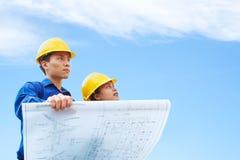 De holding van de contractant de bouwplan stock foto