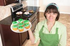De holding van de gezinshulp cupcakes stock afbeelding