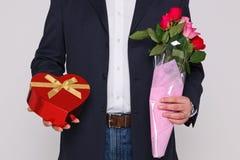 De holding van de mens bloeit en een doos chocolade stock fotografie