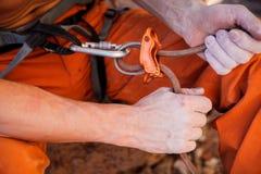 De holding van de rotsklimmer maakt kabel vast - handenclose-up Stock Afbeelding