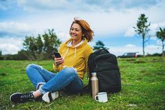 De holding van de glimlachvrouw in de vrouwelijke technologie van het handengadget, sms-bericht van het toeristen het jonge meisj stock foto