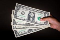 De holding van de hand ons dollars stock afbeeldingen