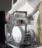 De holding van het afwasmachinedienblad door de mens stock afbeeldingen