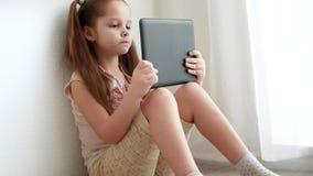 De holding van het babymeisje en het gebruiken van PC-tablet en zitten op de vloer in ruimte stock videobeelden