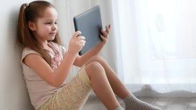 De holding van het babymeisje en het gebruiken van PC-tablet en zitten op de vloer in ruimte stock footage