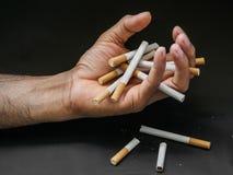 De holding van de mensenhand en vernietigt sigaretten op zwarte achtergrond Qui royalty-vrije stock afbeelding