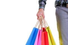 De holding van de mensenhand het winkelen zakken op witte achtergrond worden geïsoleerd die Stock Afbeeldingen