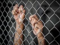 De holding van de mensenhand op de omheining van de kettingsverbinding om Rechten van de mens DA te herinneren royalty-vrije stock fotografie